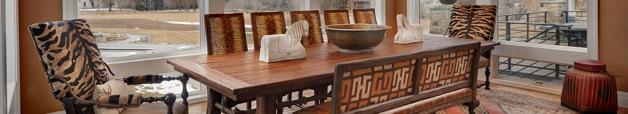 A large wooden dining room table with animal print chairs
