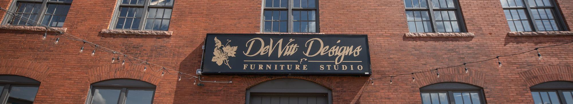The brick exterior of DeWitt showroom with black sign that reads DeWitt Designs