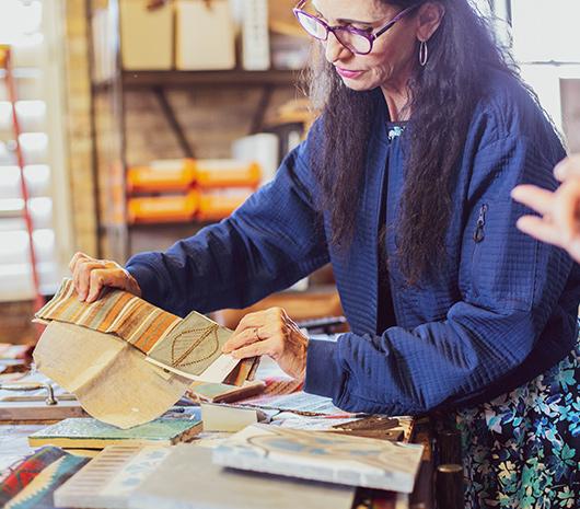 Sarah DeWitt holding up fabric samples