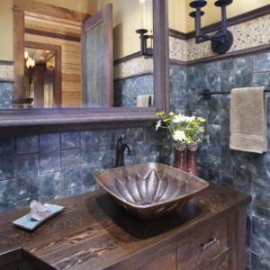 Close up of dark wooden bathroom vanity in front of a grey tiled wall and big mirror