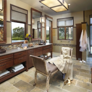 Big bathroom with tiled floors and walls and a long wooden vanity with two sinks