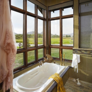 Close up of bathtub in front of a corner of windows