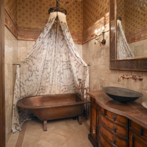 Bathroom with tiled floors and walls and patterned wallpaper and a circular shower curtain hanging above tub