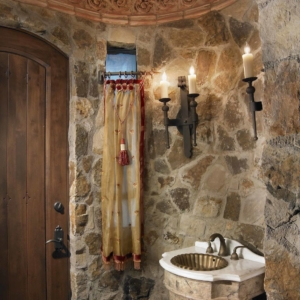 Sink against a stone wall with candles hanging above it