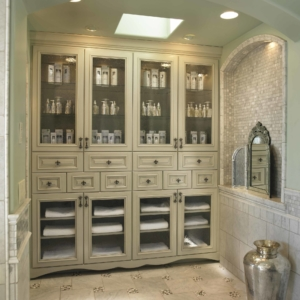 Bathroom storage in cream cabinets lining a wall with tiled floors