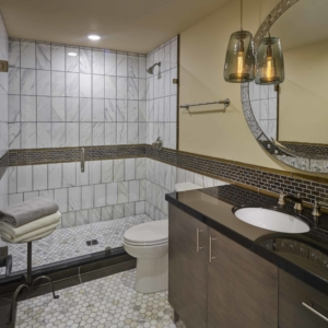 Bathroom with tiled floor and shower and a dark wooden vanity