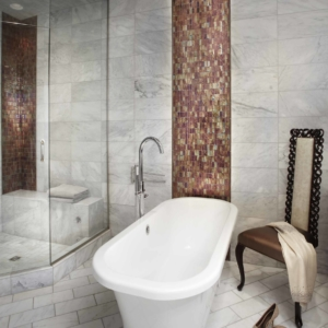 Tub in the middle of a bathroom with white tiled floors and walls