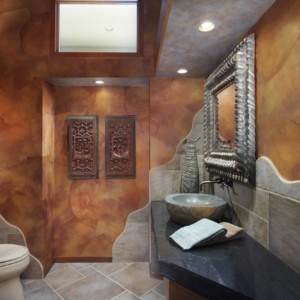 Bathroom with brown stone walls and indigenous art on the walls