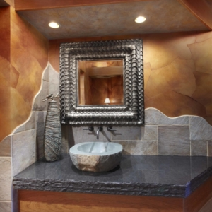 Bathroom with brown and grey stone on the walls and a square mirror hanging over the vanity