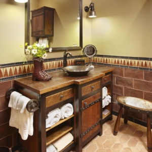 Bathroom with tiled floors and walls and a brown wooden vanity