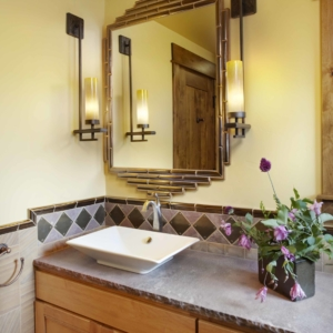 Close up of bathroom vanity with grey stone counter top and a geometric mirror hanging on the wall