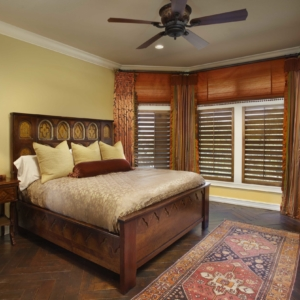 Bedroom with yellow walls and orange curtains designed by DeWitt
