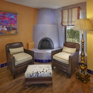 Corner of bedroom with grey clay fireplace and leather chairs