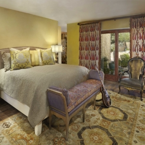 Bedroom with a mix of printed fabrics and yellow walls