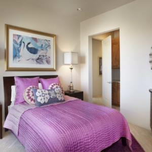 Bedroom with white walls and a bright purple comforter on the bed