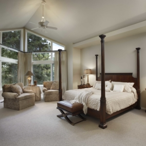 Airy, spacious bedroom with white walls and a dark wooden four-post bed
