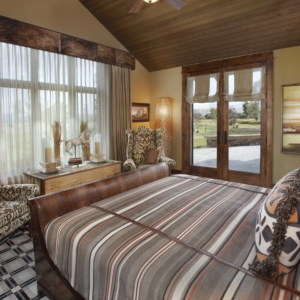 Bedroom with rich wood accents and tan walls