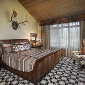 Bedroom with plaid carpet, a dark wooden and leather bed frame and antlers hanging above the bed