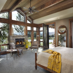 Bedroom with bed facing floor to ceiling windows overlooking a pond