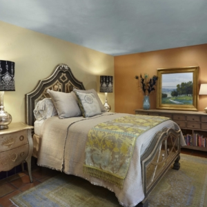Bedroom with one tan wall and one burnt orange wall and neutral bed
