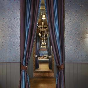 Hallway with a chandelier, mirror, purple drapes and beautiful jeweled wallpaper