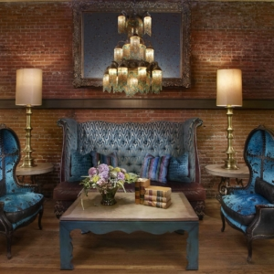 Blue velvet couch and chairs in front of brick wall
