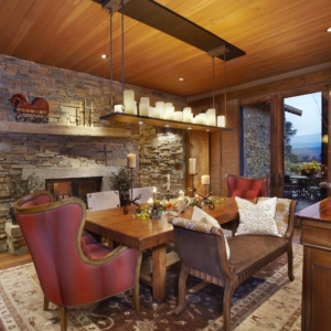 Dining room with a stone accent wall and red velvet chairs around a big wooden table