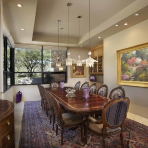 dining room with long table, neutral walls and big paintings hanging on the walls