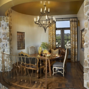 Small dining room up a couple stairs with stone wall accents in front of a window