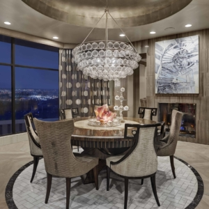 Dining room with round table and big chandelier hanging over the table