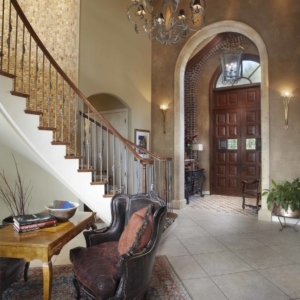 Hallway leading to grand staircase and beautiful dark wooden door