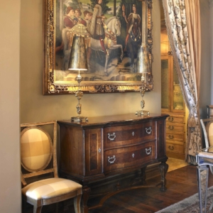 Hallway leading to big painting hanging on the wall over a wooden console table