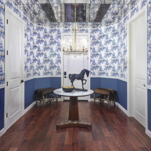 Hallway with blue and white wallpaper on walls, dark wooden floors and a circle console table in the middle