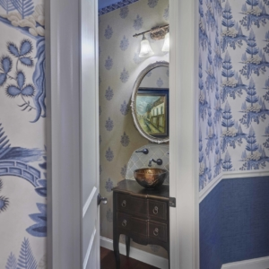 Close up of walls with blue and white wallpaper and a white door opening