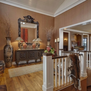 Hallway above a staircase with brown walls, wooden floors and a intricately designed console table