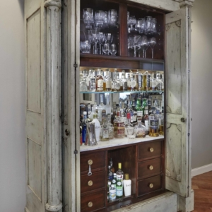 Furniture piece that opens to be a bar car with glasses and dozens of liquor bottles on the shelves