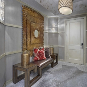 Hallway with light grey walls, light grey tiled floors and a big gold mirror art piece on the wall