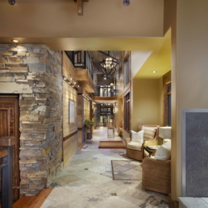 Long hallway with tiled floors, wood paneled walls and stone accents