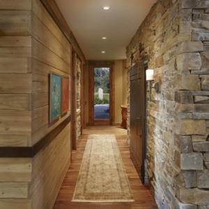 Hallway with one wood paneled wall, one stone wall and a long Persian runner on the wooden floors