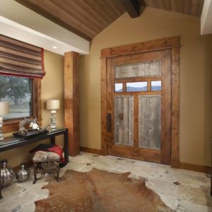 Entryway with big wooden door, tiled floor with cow rug and black console table against wall
