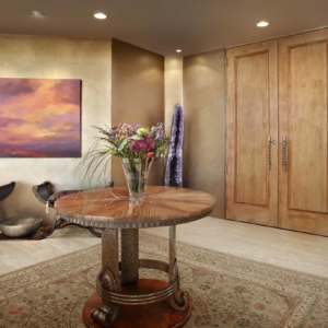 Foyer with a big square rug and a circle wooden table in the middle