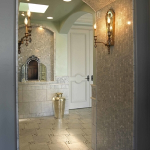 Hallway with arched ceilings and tiled walls with grey accents and lit light fixtures