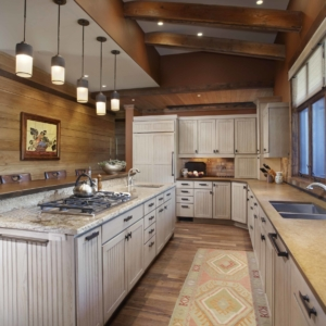 Long kitchen with white washed cabinets and dark wooden beams