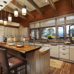 Kitchen with white washed cabinets, brown walls and dark wooden accents