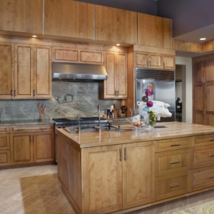 Tall wooden cabinets with stone backsplash