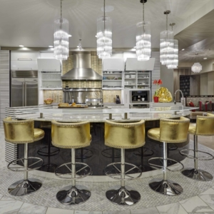 Kitchen with five chandelier hanging over the island with golden island barstools