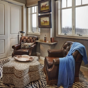 Corner of room with brown leather chairs and zebra rug