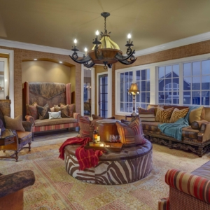 Living room with brown chairs and couches circled around a round zebra ottoman