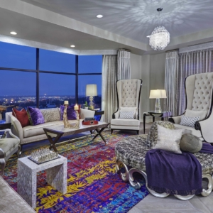 Living room overlooking a city scene with white walls, furniture and window coverings