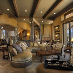 Big living room with tiled floors, yellow walls and neutral seating